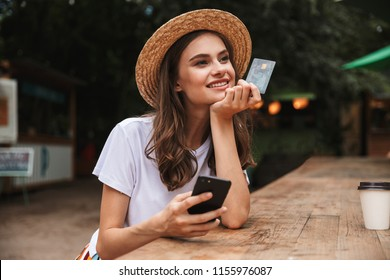 Happy young girl holding plastic credit card while using mobile phone at the cafe outdoors