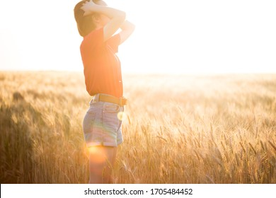 happy young girl joys at the wheat field at the evening time. sunset and atmospheric mood