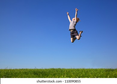 Happy young girl jumping in the meadow