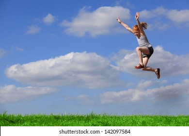 Happy young girl jumps in the meadow