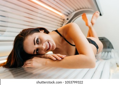 happy young girl lies in a horizontal solarium, sunbathing, wants a beautiful tanned skin