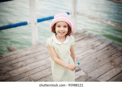 Happy young girl with lolly-pop on a pier