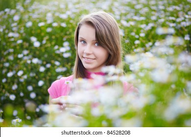 happy young girl in a meadow with camomiles