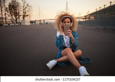 Happy young girl on the street take a photo on a smartphone. Beautiful blonde with headphones and smartphone make a selfie. outdoors