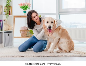 Happy young girl petting golden retriever dog ears while sitting on light room floor
