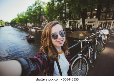 Happy young girl photographer takes selfie near canals in Amsterdam, Netherlands. Pretty female student travels abroad and takes pictures for her blog.