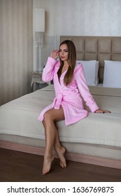 Happy young girl in a pink bathrobe sits on the bed