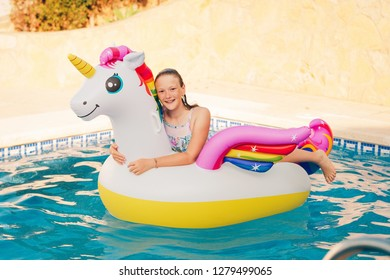 Happy young girl playing in the pool, relaxing on inflatable colorful unicorn