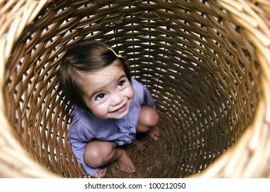 Happy young girl plays peekaboo and hides inside a basket.Concept photo of child , children, childhood, happy, happiness, health, love, care, free, freedom. Real people. Copy space