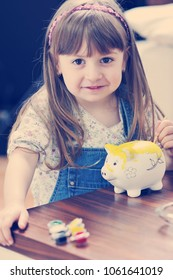 happy young girl  portrait at home while painting piggy bank and representing banking and finance concept