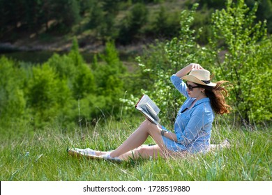 Happy young girl reading book. Beautiful young girl resting on lawn. Young woman in hat