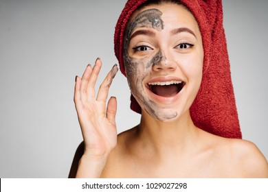 happy young girl with a red towel on her head applied a clay mask to half of her face, laughs, spa procedures