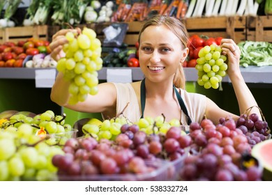 Happy young girl seller wearing apron holding bunch of grapes on market
