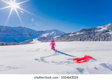 Happy young girl sledding in a sunny winter alpine landscape