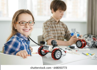 Happy young girl smiling to the camera joyfully her brother building electronic robot on the background copyspace education science hobby leisure happiness children science learning school classmates
