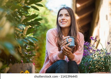 Happy young girl smiling and looking side, sitting on home terrace, holding a mug drinking a hot beverage Hobby and resting leisure concept.