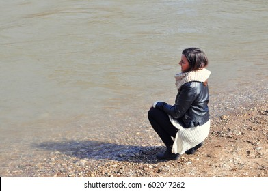 Happy young girl squatting by the river and watch a water