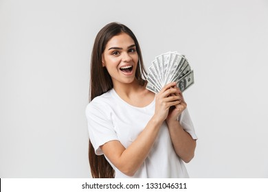 Happy young girl standing isolated over white background, showing money banknotes
