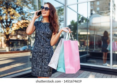 Happy young girl in sunglasses enjoying shopping in town and talking on phone