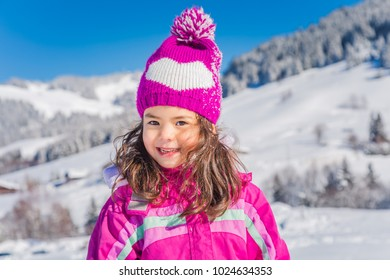 Happy young girl in a sunny winter alpine landscape