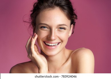 Happy young girl touching her perfect skin on pink background. Beauty & Skin care concept