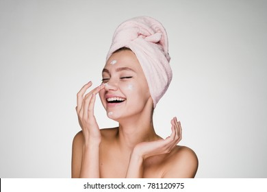 happy young girl with a towel on her head apply a cleansing mask on her face