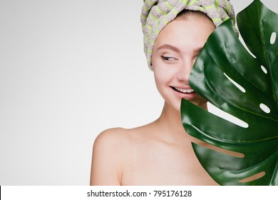 happy young girl with a towel on her head holds a green leaf, thinks about beauty