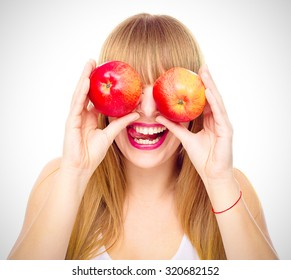 Happy  young girl with two apples near her eyes shows tongue , isolated on white
