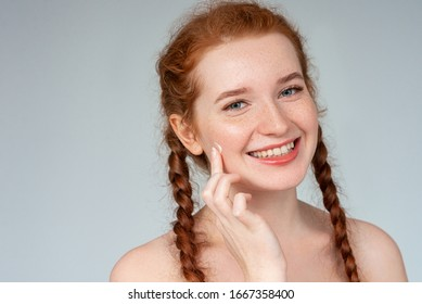 Happy young girl using cream. Natural beauty, face skin care, cosmetic advertising concept. Close up portrait. Copy, empty space for text