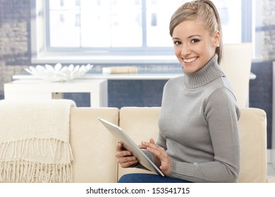 Happy young girl using tablet computer, smiling, looking at camera.