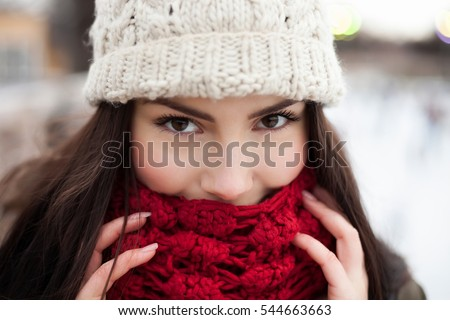 0bd61762c5409 Happy young girl warming up in warm winter clothes.Smiling young woman  cover her face
