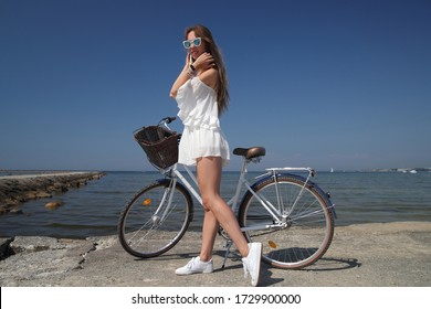 happy young girl in white dress with bicycle