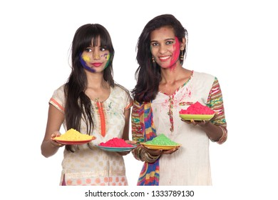 Happy young girls having fun with colorful powder at Holi festival of colors