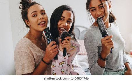 Happy young girls having fun singing songs in karaoke style holding hair brushes and remote control. Girls at a sleepover having fun singing together.