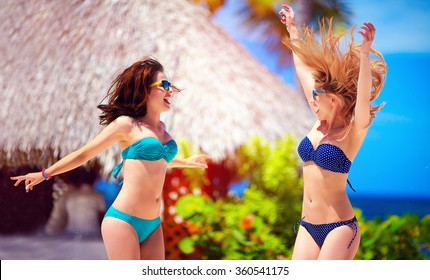 happy young girls jumping on tropical beach, summer vacation