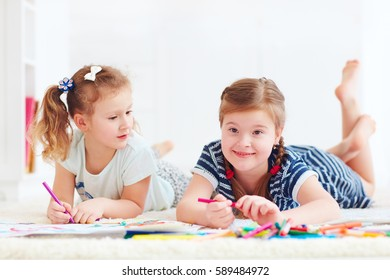 happy young girls, kids painting with felt pen together