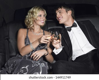 Happy young glamorous couple toasting champagne in limousine
