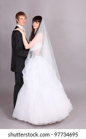 Happy young groom and beautiful bride embrace and look at camera in studio on gray background