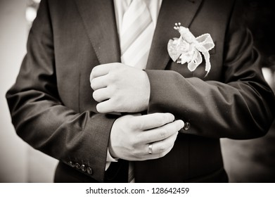 Happy young groom on their wedding day. Handsome groom thinking and putting on his bowtie while getting dressed for his wedding. Handsome caucasian man in tuxedo