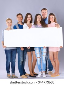 Happy young group of people standing together and holding a blank