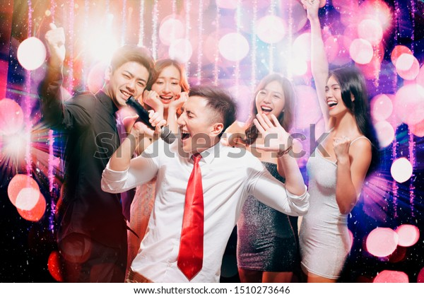 happy young group singing and dancing in party