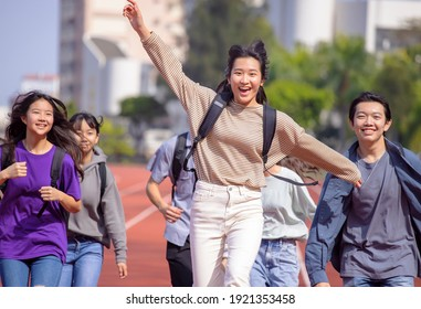 Happy young group students running Across Field