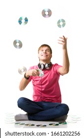 Happy young guy a music lover with headphones sits on the floor and juggles compact discs on a white background. Concept of modern and outdated music media