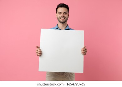 happy young guy smiling and holding empty board, standing on pink background