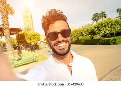 Happy young guy take selfie in sunglasses during holiday life moment. Hipster traveler wanderers enjoying exclusive alternative destination make souvenir photo during vacation in Marrakech.