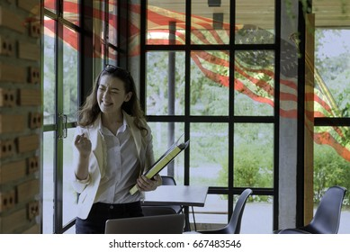 Happy young half Thai-American woman in happy moment with black text file with  American flag blowing in the wind.4th July Independence day.