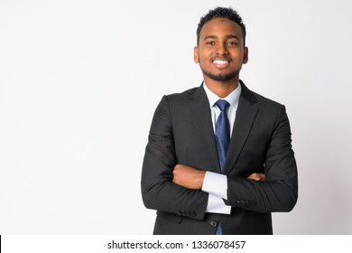 Happy young handsome African businessman smiling with arms crossed