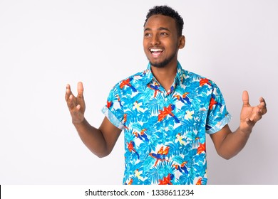 Happy young handsome African tourist man looking surprised