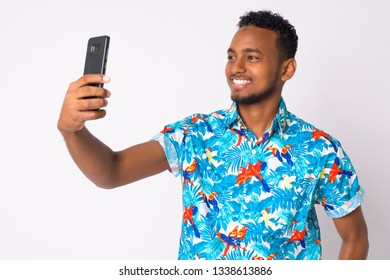Happy young handsome African tourist man taking selfie