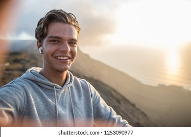 Happy young handsome guy, making selfie portrait on a mountain hill in sunset light.